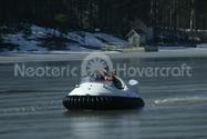 Photo Recreational Hovercraft flying over partially frozen water